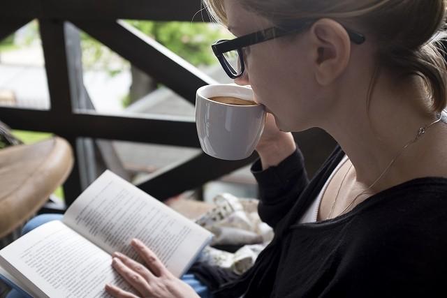 天使のララをコーヒーに入れて飲む女性